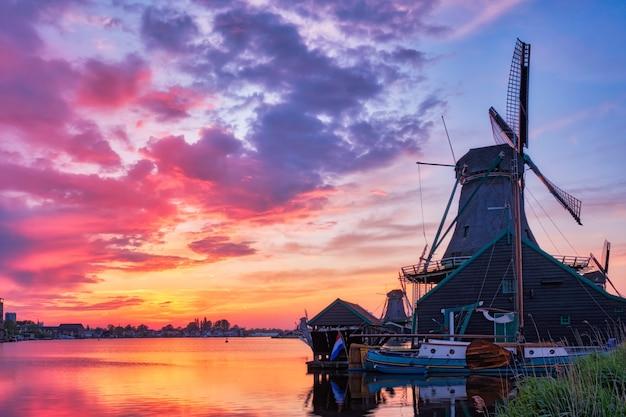 Cena rural da holanda - moinhos de vento no famoso local turístico zaanse schans na holanda, no pôr do sol com céu dramático. zaandam, holanda Foto Premium