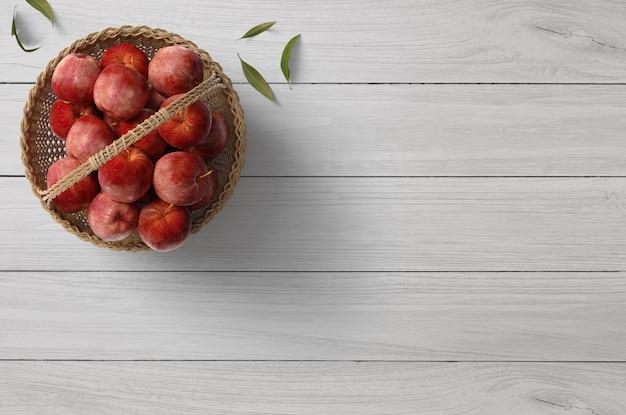 Cena simples de uma mesa de madeira clara com uma cesta de maçãs vermelhas frescas e folhas verdes Foto Premium