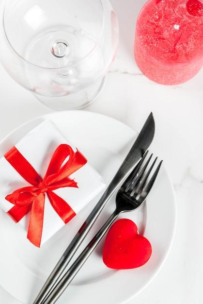 Cenário de mesa de dia dos namorados com prato, garfo, faca, caixa de presente e coração vermelho, em mármore branco copyspace Foto Premium