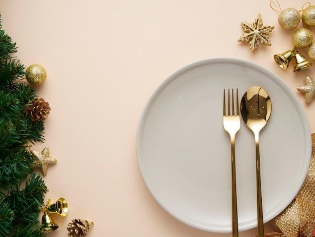Cenário de mesa de jantar de natal com enfeites de ouro Foto Premium