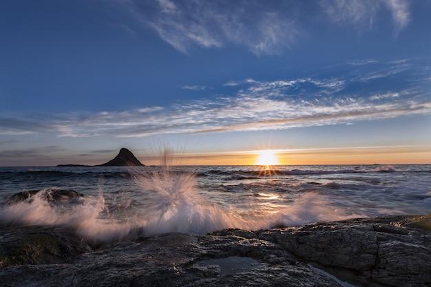 Cenário de tirar o fôlego com a água caindo na costa durante o belo nascer do sol Foto gratuita