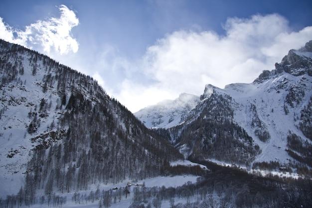 Cenário de tirar o fôlego das montanhas cobertas de neve sob um céu nublado panorâmico Foto gratuita