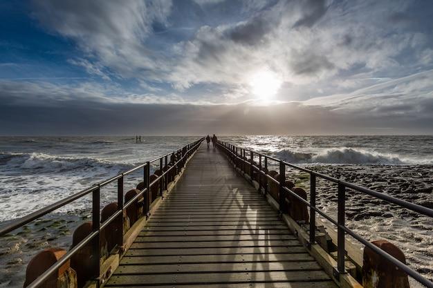 Cenário de tirar o fôlego de um nascer do sol sobre o cais do oceano em westkapelle, zeeland, holanda Foto gratuita