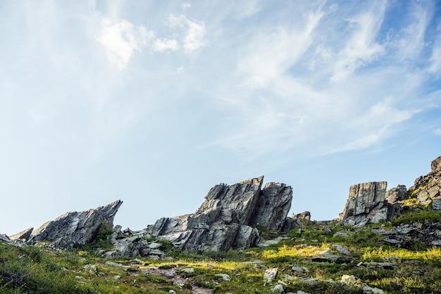Cenário ensolarado das montanhas com pedras afiadas de forma incomum. impressionante paisagem montanhosa cênica com grandes pedras pontiagudas rachadas closeup entre grama sob o céu azul na luz solar. rochas pontiagudas com rachaduras Foto Premium