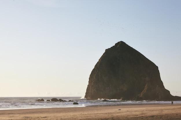 Cenário fascinante do pôr do sol em haystack rock no oceano pacífico, oregon Foto gratuita