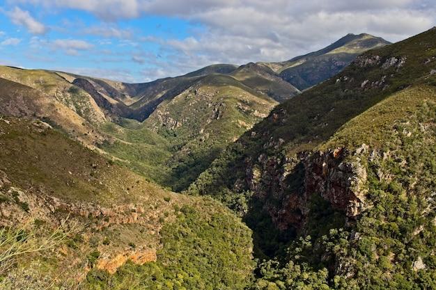 Cenário montanhoso hipnotizante coberto de verde sob o céu nublado Foto gratuita