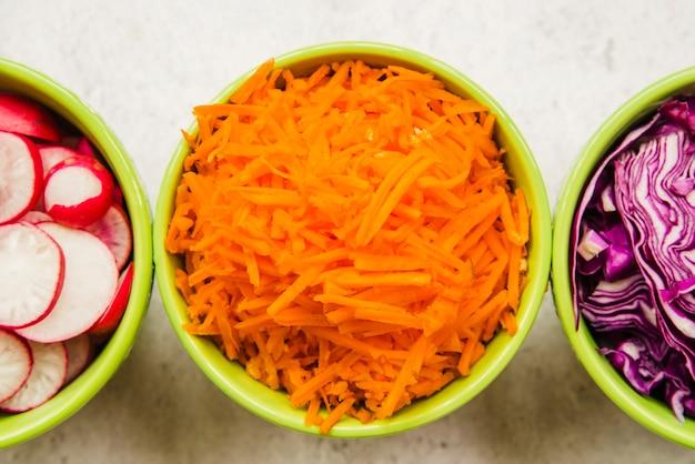 Cenoura picada fresca; repolho e rabanete em tigela verde Foto gratuita
