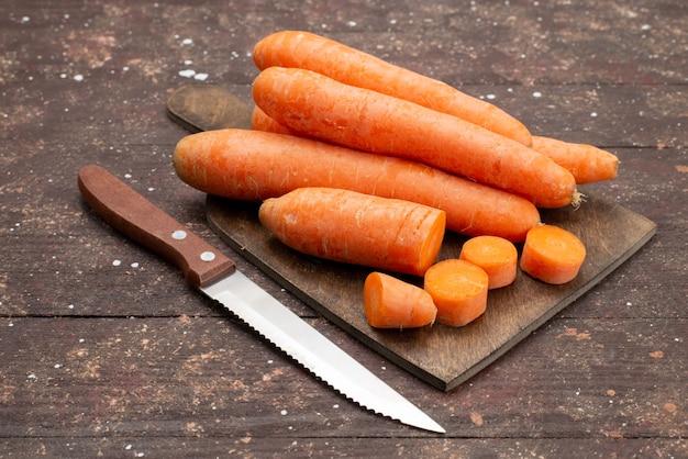 Cenouras alaranjadas da vista dianteira cortadas e inteiras no marrom Foto gratuita