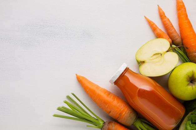 Cenouras, maçãs e suco com espaço de cópia Foto gratuita
