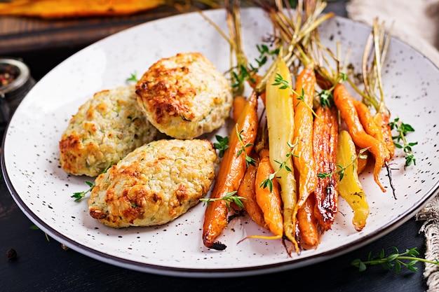 Cenouras orgânicas assadas com tomilho e costeleta de frango com abobrinha Foto gratuita