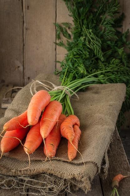 Cenouras orgânicas frescas na superfície de madeira Foto Premium