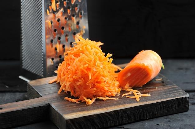 Cenouras raladas em um ralador close-up Foto Premium