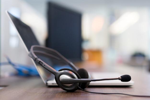 Central de atendimento de fone de ouvido hotline na mesa de ajuda do escritório de computador Foto Premium