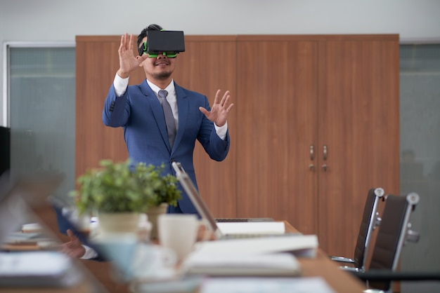 Ceo asiático de terno usando fone de ouvido de realidade virtual na sala de reuniões Foto gratuita