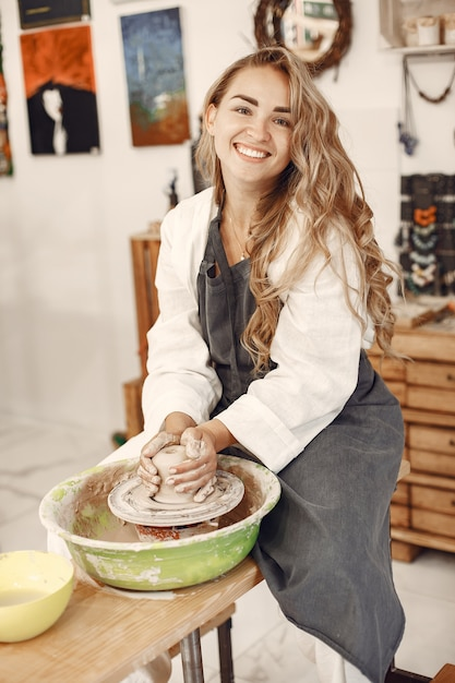 Cerâmica feminina trabalhando com argila na roda em estúdio. barro com água respingou em torno da roda de oleiro. Foto gratuita