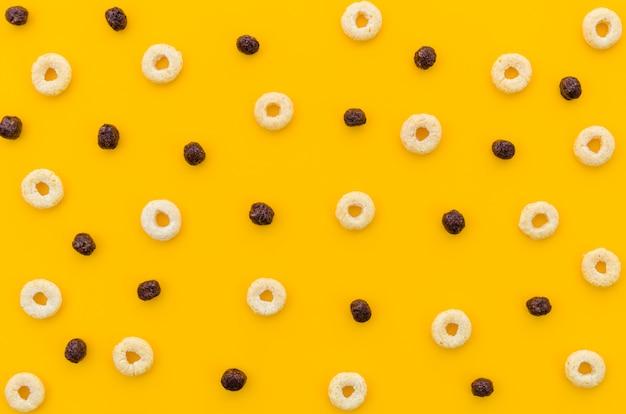 Cereais coloridos com frutado em fundo laranja Foto gratuita