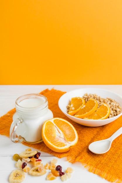 Cereais de alto ângulo com laranja e iogurte Foto gratuita