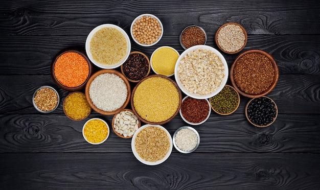 Cereais, grãos, sementes e grumos na superfície de madeira preta Foto Premium
