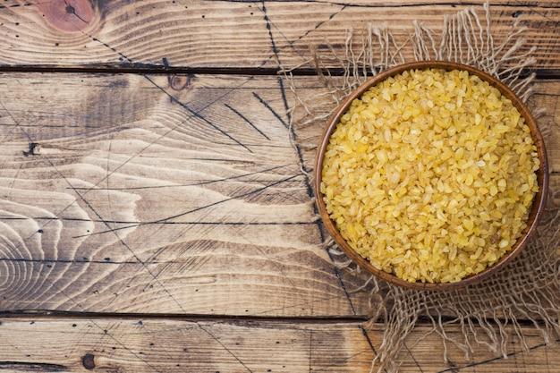 Cereal cru seco turco tradicional do bulgur em uma bacia de madeira. Foto Premium