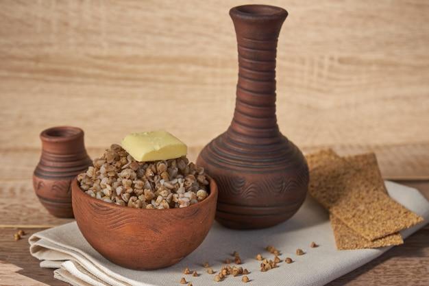 Cereal de trigo sarraceno cozido na tigela de barro marrom na mesa de madeira. grãos sem glúten para uma dieta saudável Foto Premium