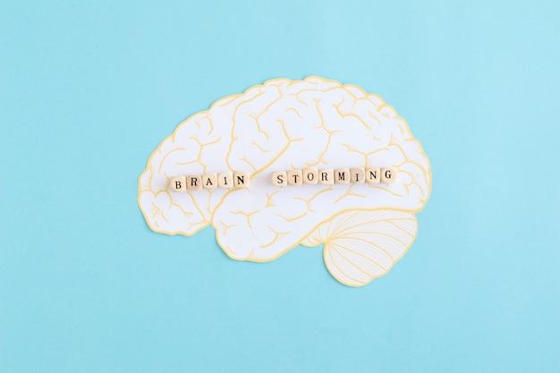 Cérebro atacando blocos sobre o cérebro branco contra o fundo azul Foto gratuita