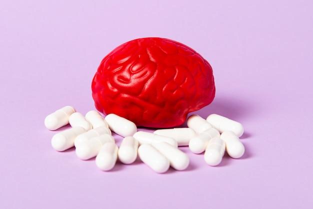 Cérebro vermelho em um fundo rosa com comprimidos brancos. algumas pílulas para o cérebro. Foto Premium