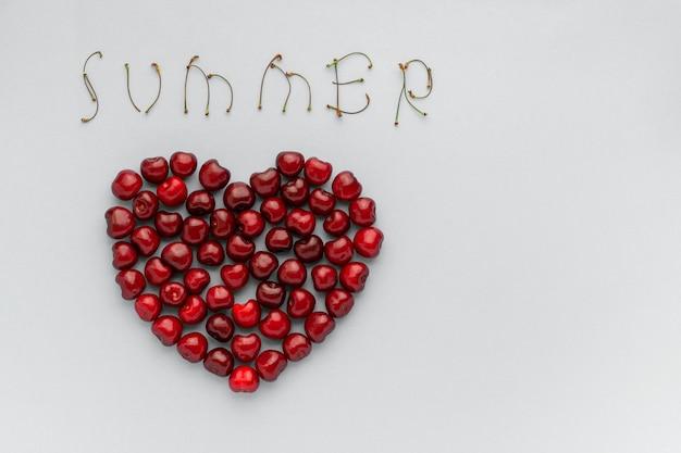 Cerejas de bagas vermelhas em forma de coração e texto verão Foto Premium