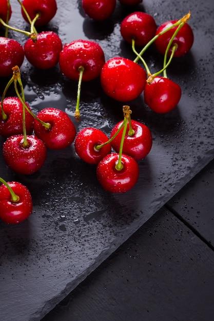 Cerejas em uma placa de ardósia. bagas vermelhas em gotas de água em quadros pretos. comida saudável. vista do topo. copyspace Foto Premium