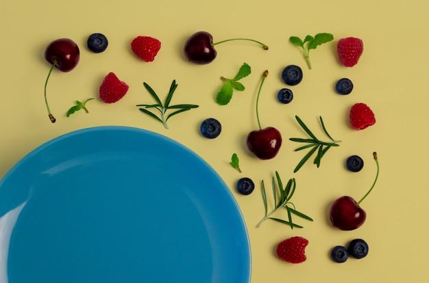 Cerejas frescas, mirtilos, framboesas, hortelã e alecrim folheiam na vista superior com placa azul e fundo de cor amarelo pastel. Foto Premium