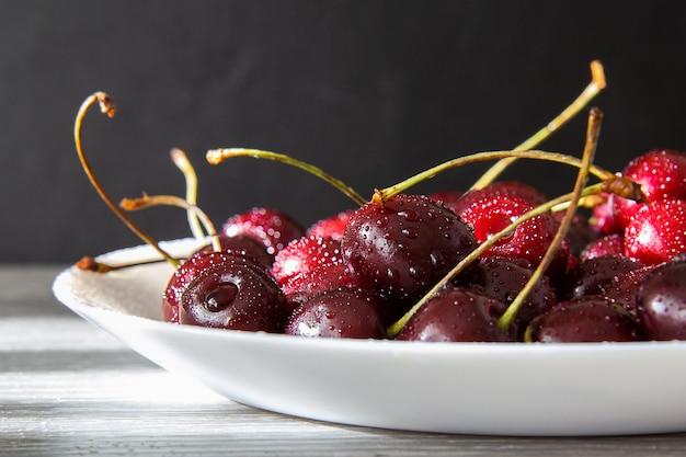 Cerejas maduras em um prato branco em cima da mesa. Foto Premium