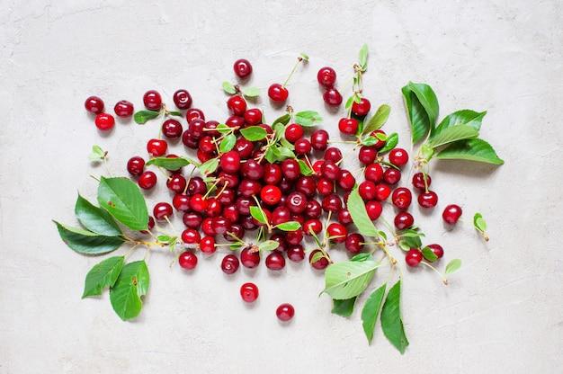 Cerejas maduras frescas com folhas na mesa cinza texturizada Foto Premium