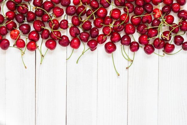 Cerejas vermelhas em madeira branca Foto gratuita