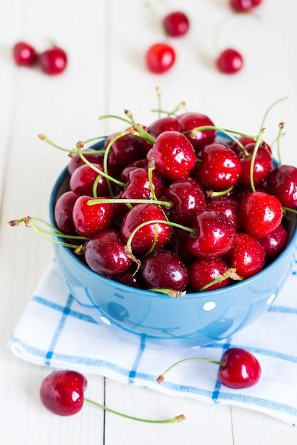 Cerejas vermelhas na tigela em madeira branca na toalha azul Foto gratuita
