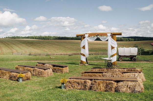 Cerimônia de casamento na rua no campo da aldeia. decoração com palheiros e um carrinho para um casamento. Foto Premium