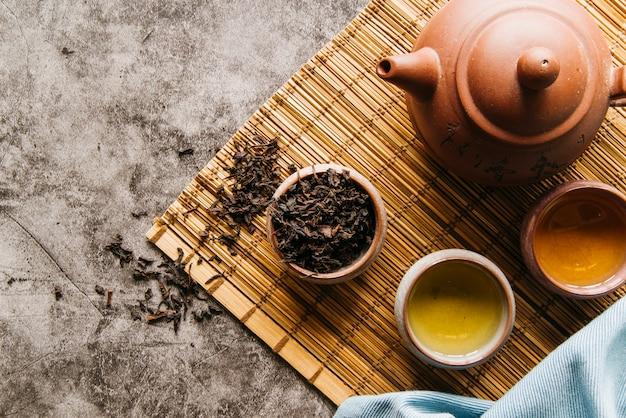 Cerimônia de chá tradicional acessórios com bule e xícara de chá no placemat Foto gratuita