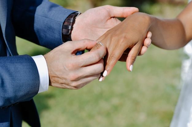 Cerimônia de colocar a aliança no dedo da noiva ao ar livre Foto gratuita
