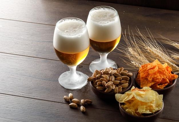 Cerveja com espuma em copos de cálice com pistache, espigas de trigo, batatas fritas vista de alto ângulo em uma mesa de madeira Foto gratuita