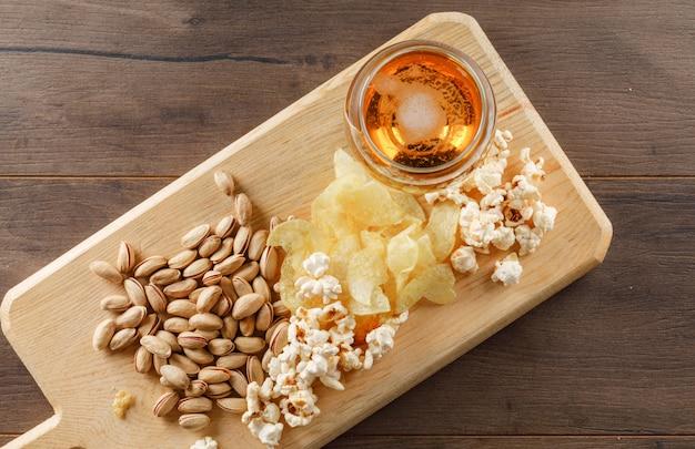 Cerveja com lanche em um copo de cálice na mesa de madeira e tábua, vista superior. Foto gratuita