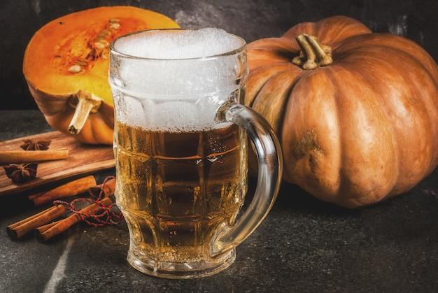 Cerveja de abóbora picante espumante ou cerveja em caneca de vidro, em fundo preto Foto Premium