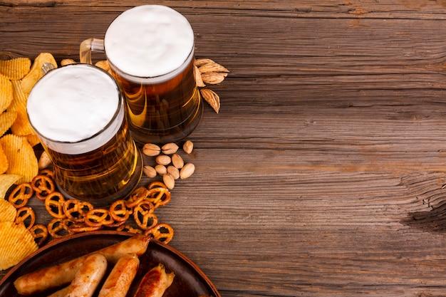 Cerveja de close-up com lanches na mesa de madeira Foto gratuita