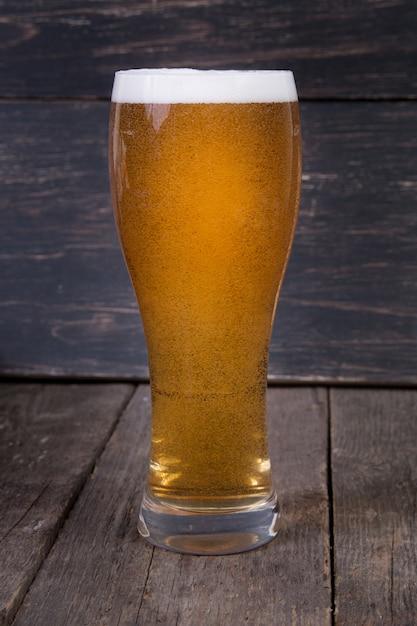 Cerveja de lager em um copo na mesa de madeira escura Foto Premium