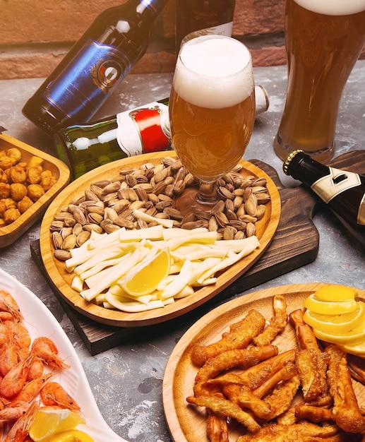 Cerveja e petiscos de cerveja pilsen na tabela de madeira. nozes, queijo chips, pistachios, crevettes Foto gratuita