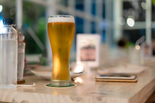 Cerveja em um copo alto que é colocado sobre a mesa. Foto Premium