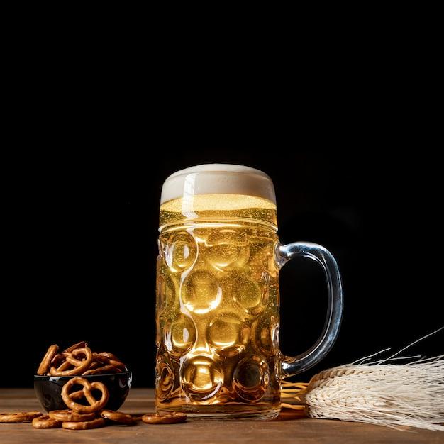 Cerveja loira close-up em uma mesa com pretzels Foto gratuita