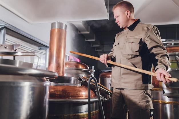 Cervejeiro na cervejaria derramando o malte no tanque. Foto Premium