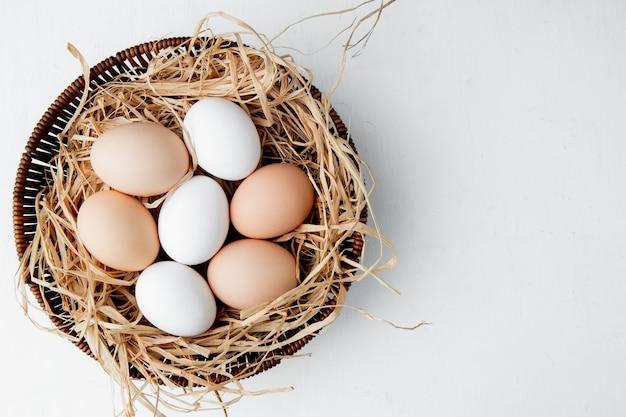 Cesta cheia de ovos no ninho na mesa branca Foto gratuita