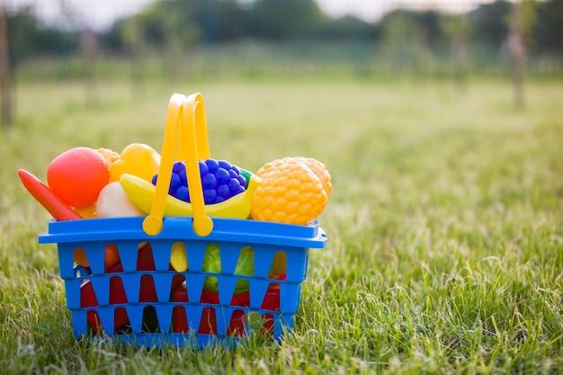 Cesta colorida plástica brilhante com frutas e legumes de brinquedo ao ar livre num dia de verão ensolarado. Foto Premium