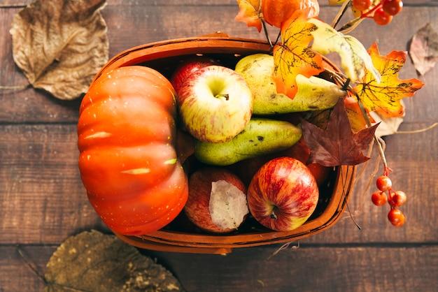 Cesta com colheita outonal na mesa Foto gratuita