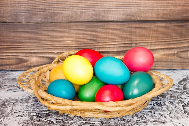 Cesta com ovos de páscoa no fundo de tábuas de madeira Foto Premium