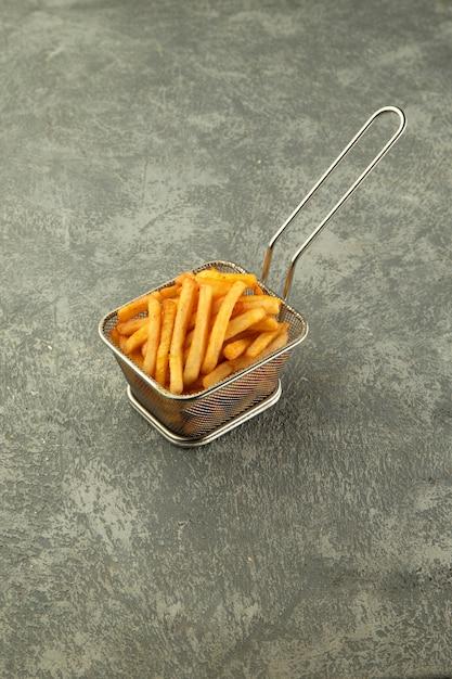 Cesta de aço de batatas fritas no fundo cinza liso Foto gratuita